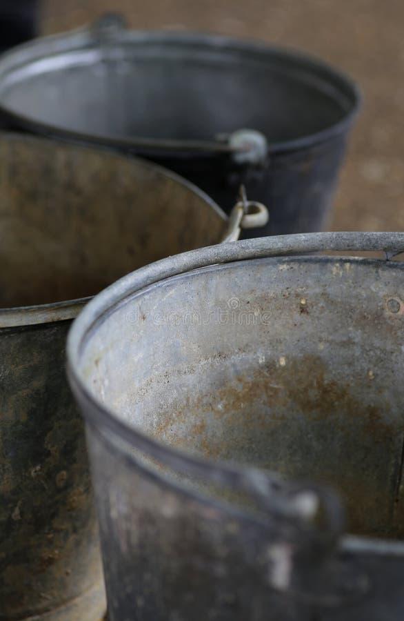 Old tin metal vintage buckets. Three old tin rusty metal vintage buckets stock images