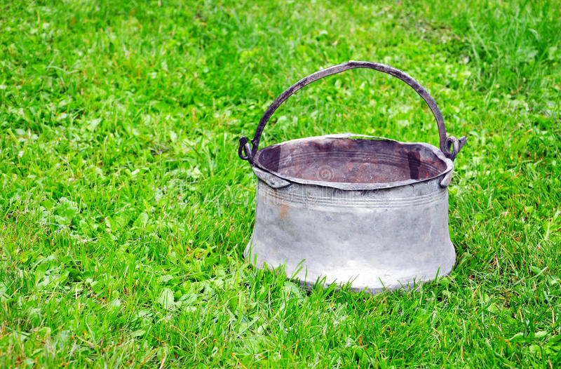 Old tin pail. On the green grass royalty free stock images