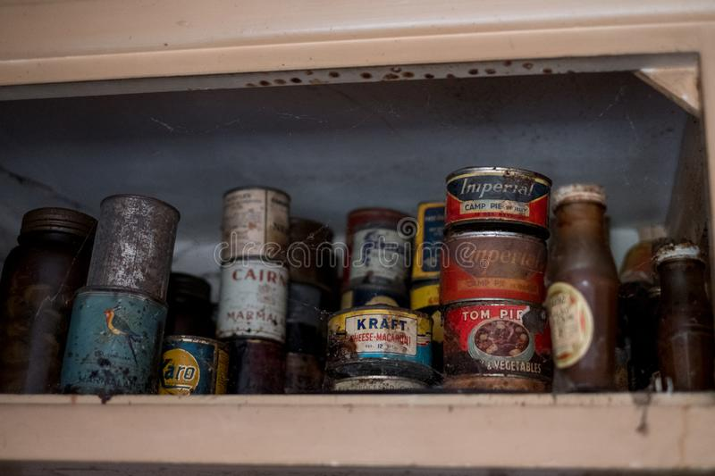Old tins of food in cupboard in kitchen in derelict house. Harrow UK. Old tins of food in cupboard in kitchen in derelict house, Rayners Lane, Harrow, Middlesex stock image