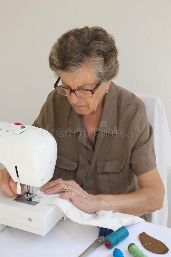 An old tired woman who is working on a sewing machine. An old tired woman between 70 and 80 years old is working on a sewing machine. Sewing items are on a royalty free stock photography