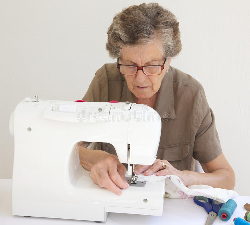 An old tired woman who is working on a sewing machine. An old tired woman between 70 and 80 years old is working on a sewing machine. Sewing items are on a stock images