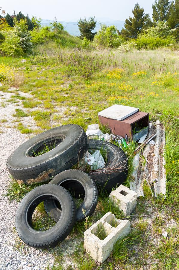 Trash in the country. Old tires left in the Nature by disrespectful people, in the Italian countryside royalty free stock photography