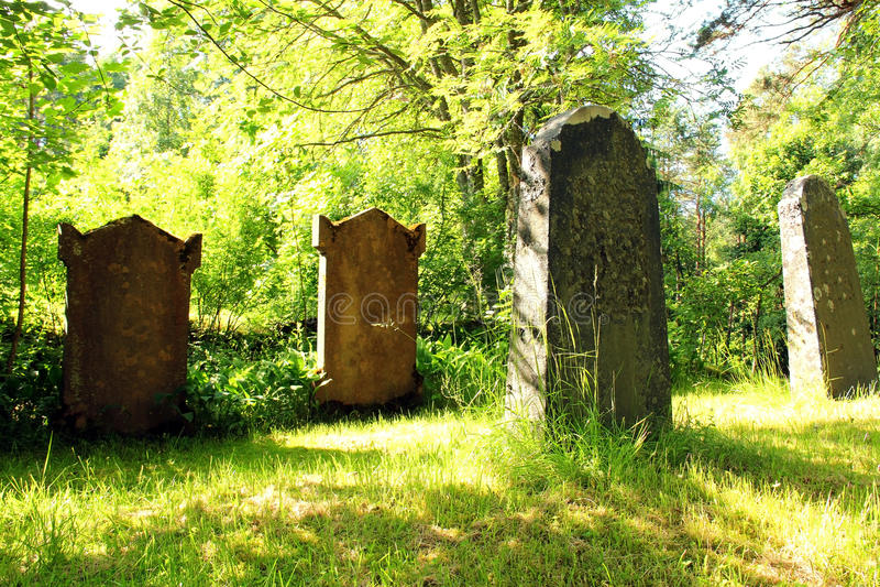 Old Tombstones at Church Yard at Midsummer. Old gravestones at the corner of a green church yard in Midsummer sunlight royalty free stock photography