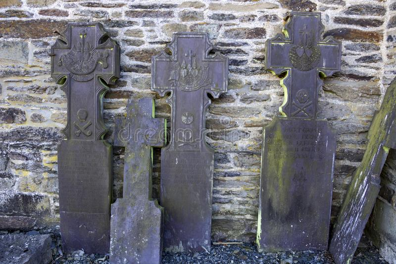 Old tombstones leaning against exterior church wall stock image