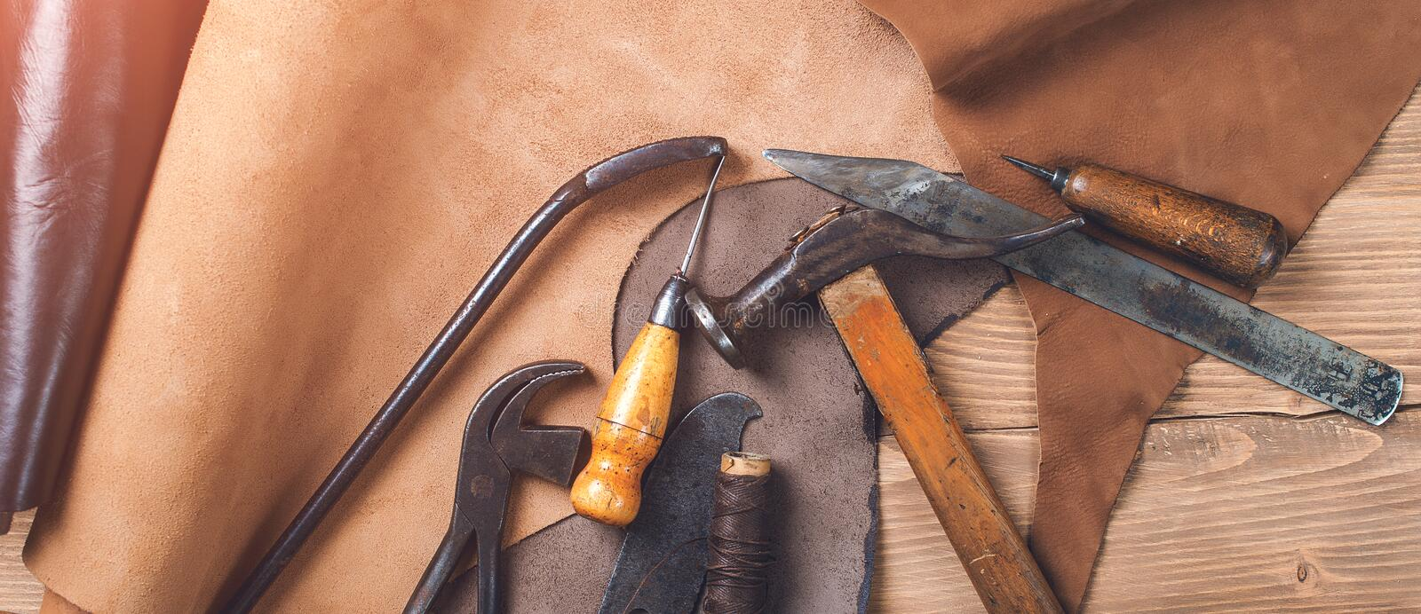 Old tools and leather at cobbler workplace. Shoemaker`s work desk. Flat lay, top view. Set of leather craft tools on wooden backg. Round. Shoes maker tools stock photos