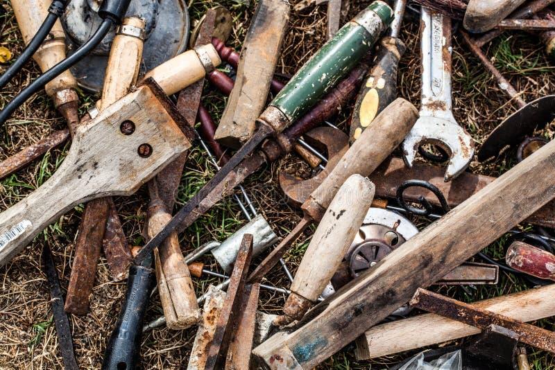 Old tools ready for garbage or recycling at garage sale for Caseta de herramientas segunda mano