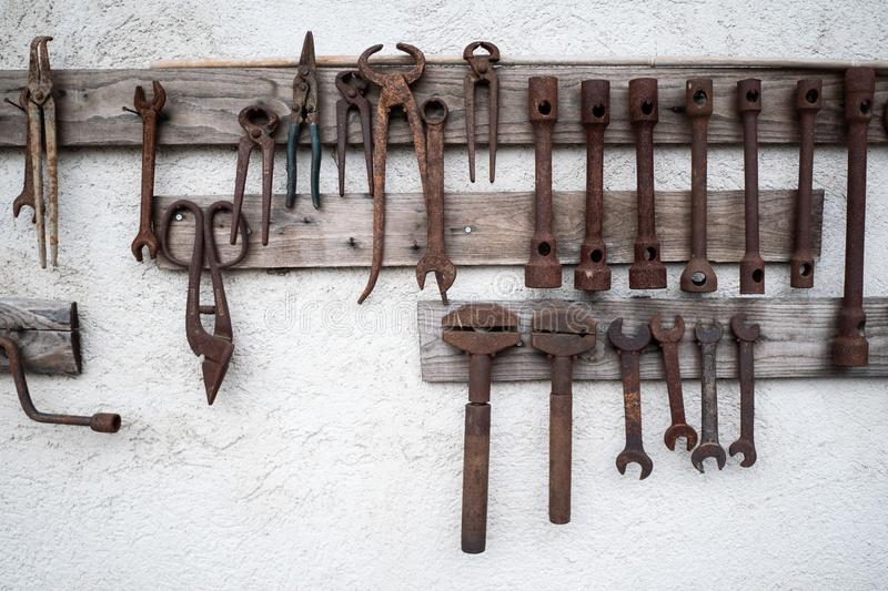 Old tools on a white wall royalty free stock image