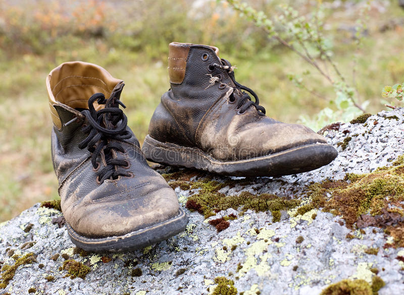 Old torn leather boots. Standing on a stone, the old torn leather boots royalty free stock photo