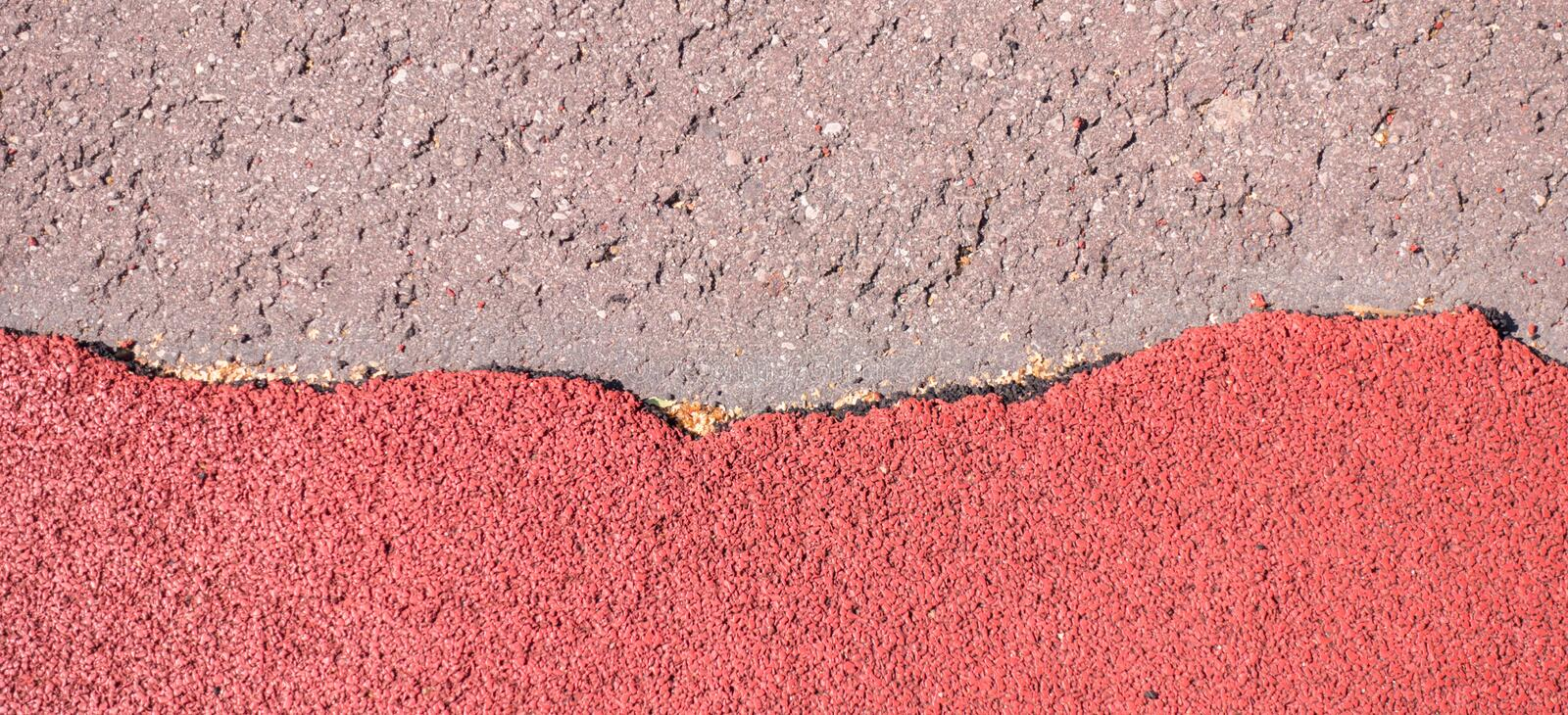Old torn red rubber crumb cover, treadmill or running track surface outdoor playground stadium texture background. Old torn red rubber crumb cover, treadmill or royalty free stock images