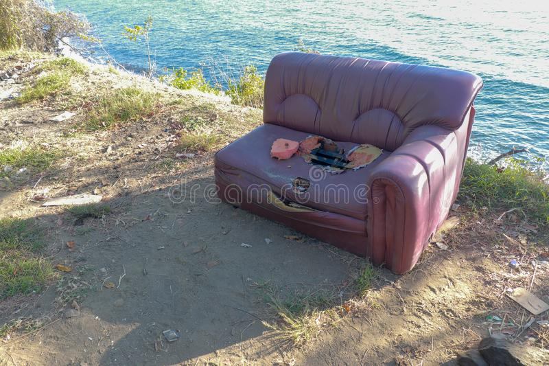 Old torn sofa with burgundy color. Red ruined couch on sea shore. Hole in seat and torn foam. Abstract composition of old couch. Nature and sea surface in stock images