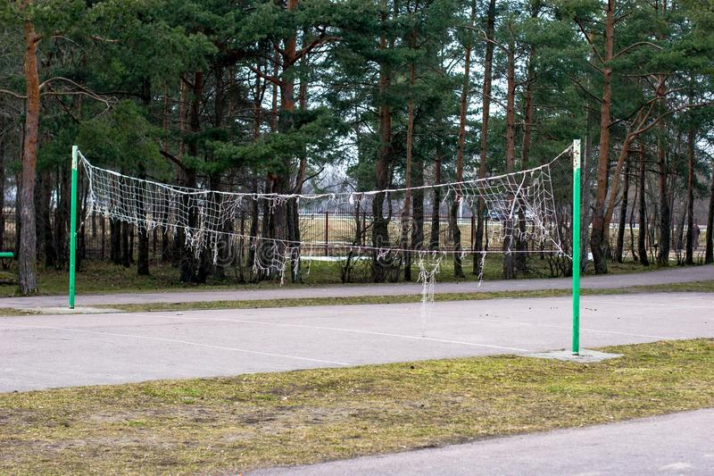 Old torn volleyball net on the street in the park in the fall. royalty free stock photos