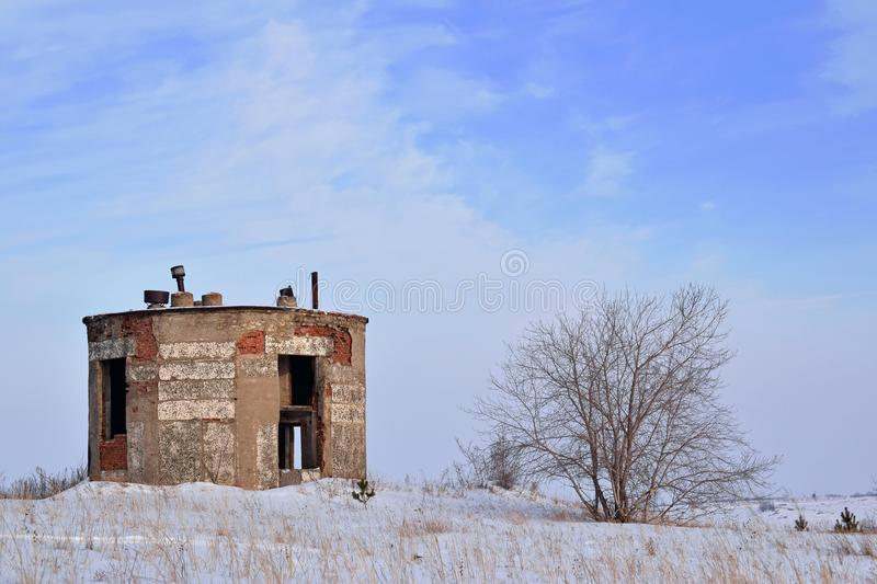 Old brick tower and wood. The old tower stands next to a tree. Winter, Sunny day and blue sky royalty free stock photos