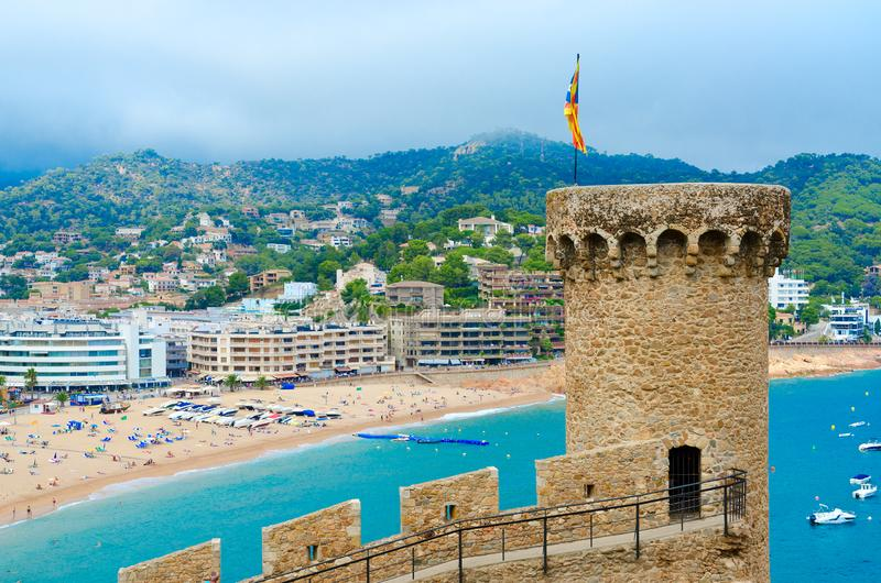 Old tower and stone fortress walls against background of resort town of Tossa de Mar, sea and mountains, Spain royalty free stock images