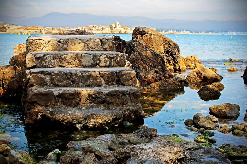 Old tower stone stairs  in blue sea water background with rocks and mountain on the horizon. Old tower stone stairs isolated in blue sea water background with royalty free stock images