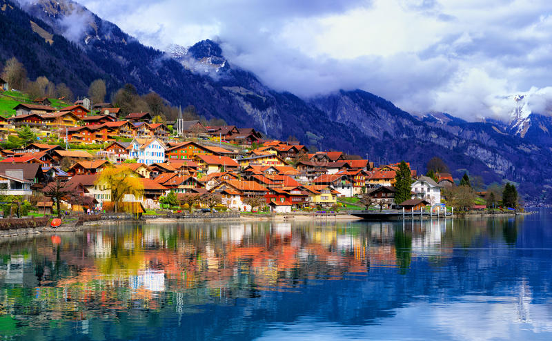 Old town and Alps mountains reflecting in lake, Switzerland royalty free stock images