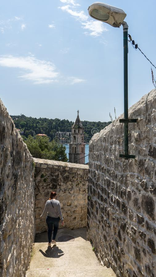 Old town bell tower sea view. Cavtat small coast village. Summer area with narrow stone streets and woman walking in between stone. Stairs. Croatia resort royalty free stock photos