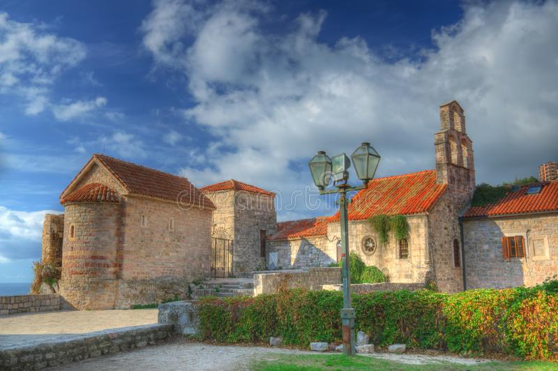 Old Town Budva, Montenegro. Beautiful picture with ancient church, cloudy sky, and sunnies and shadows colors stock image