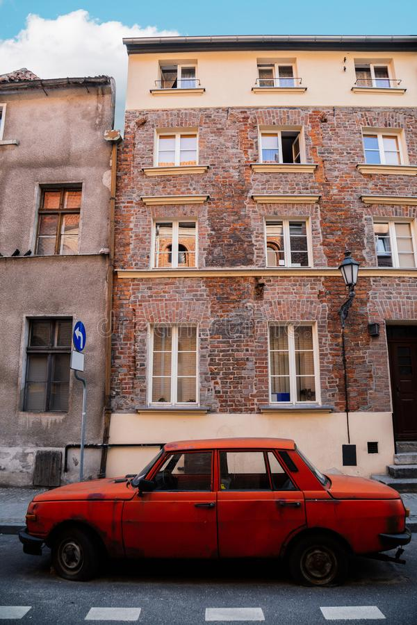Old town building and red old car in Torun, Poland stock image