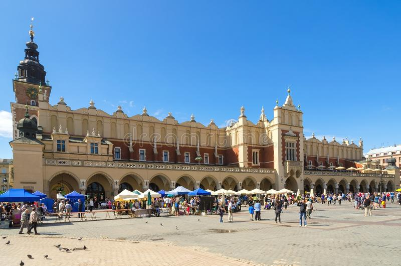 Old town in Cracow, Poland. CRACOW, POLAND - AUGUST 16, 2014: Tourists visiting the main market square in Cracow (Poland), which is one of the most famous and stock photo