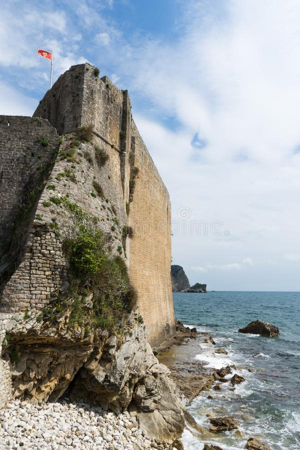 Old Town and Fort Wall at Adriatic Sea in Budva, Montenegro. Outside walls quiet sea hedging the beach. Blue sky with white cloud stock photo