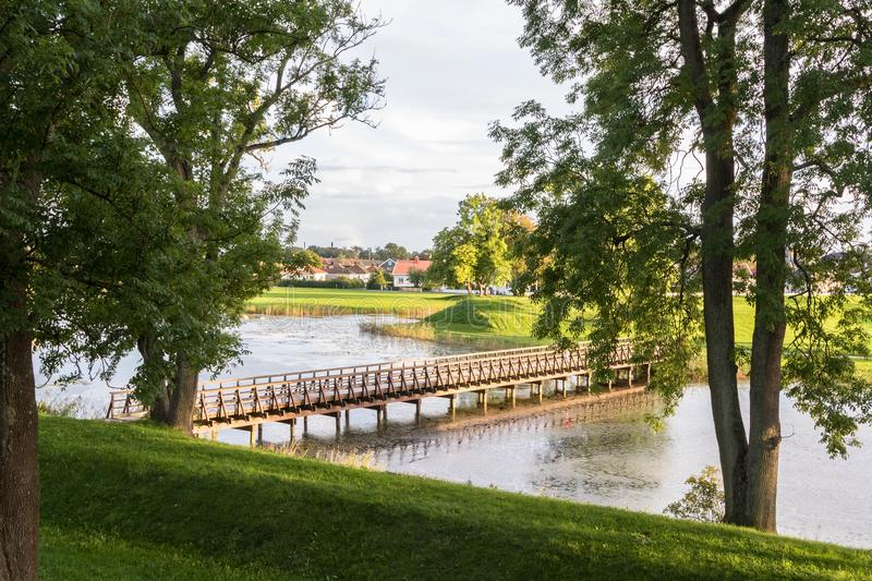 Bridge over the moat, in the old town in Fredrikstad, Norway. The Old Town in Fredrikstad, bridge over the moat. Green trees and grass. Norway royalty free stock photography