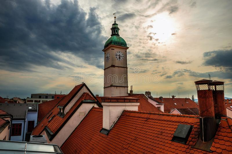 Old town hall tower and building roofs, Uherske Hradiste. View of the old town hall tower with clock and building roofs at sunset. Historical town Uherske royalty free stock image