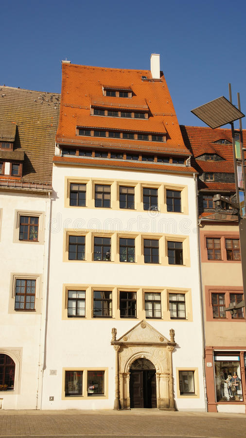 Old town house. Historical townhouse with red tiled roof and more-storey dormers on the Obermarkt in Freiberg in Saxony, Germany, deep blue and cloudless sky stock images