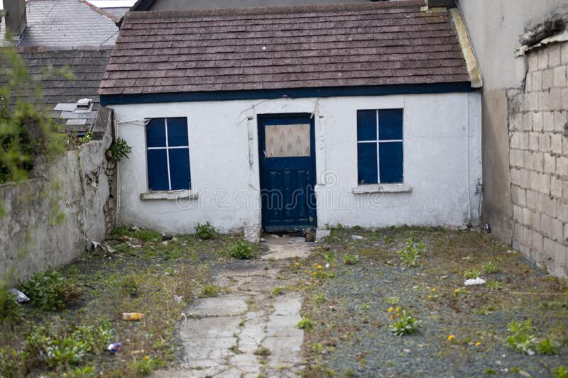 Old town house in Ireland, White walls, bright vibrant blue, Wooden window frames and door. Europe royalty free stock image