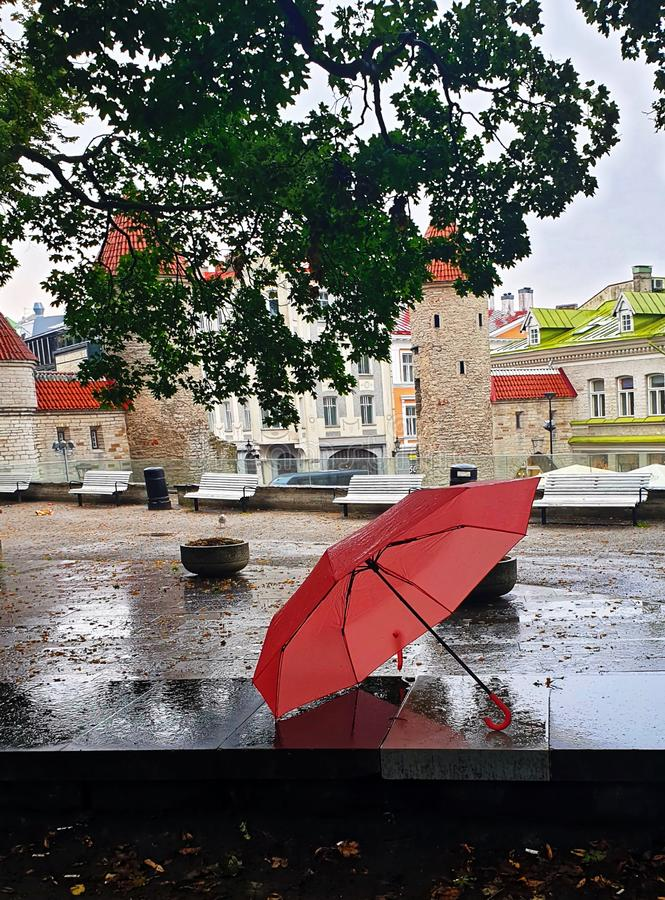 Pink Umbrella on Street cafe wet asphalt  coral  on wet rain drops evening  light   Rainy Autumn relax in Old Town empty ci. Old town Pink Umbrella on Street wet royalty free stock image