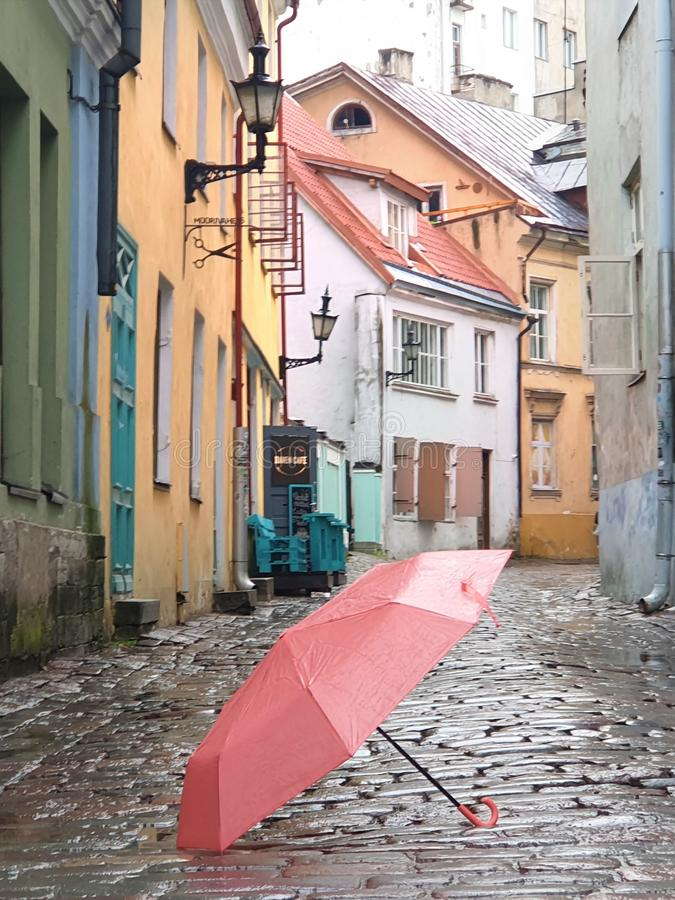Pink Umbrella on Street cafe wet asphalt  coral  on wet rain drops evening  light   Rainy Autumn relax in Old Town empty ci. Old town Pink Umbrella on Street wet royalty free stock photo