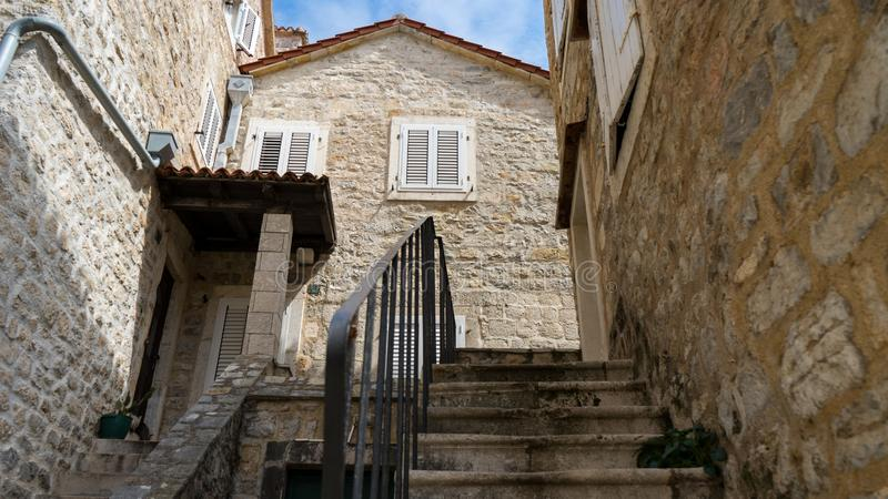 Old town, stone building in the narrow streets. The tiny staircase leads to the old house. The courtyard of one of the houses in. The Old Town of Budva royalty free stock photography