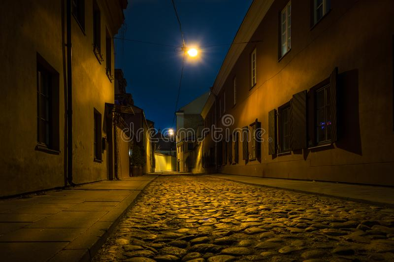 Old town street at night. Stoned old town street at night with dark blue sky and street light royalty free stock photo