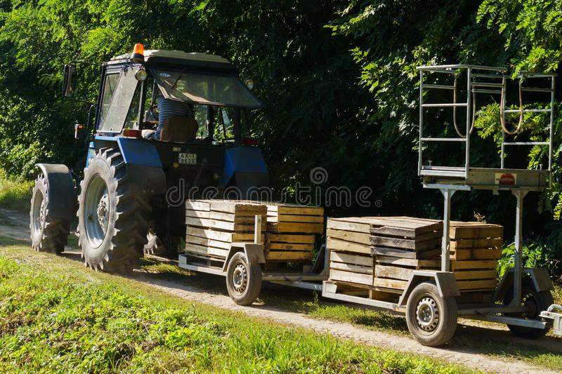 Old tractor with a device for harvesting apples. Boxes for harvesting.  royalty free stock images