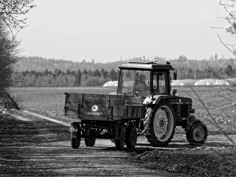 Old tractor driving through fields monochrome image royalty free stock photos
