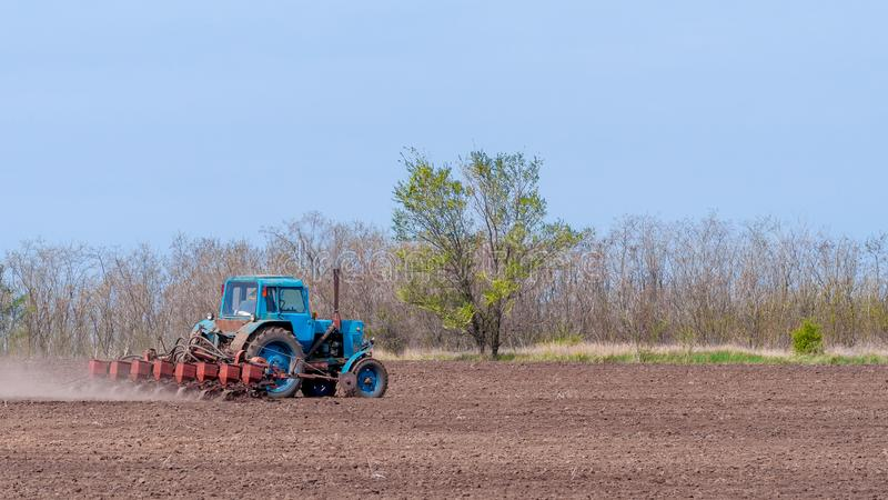 An old tractor in the field plows the land. Spring landscape of a countryside, a farm royalty free stock photography