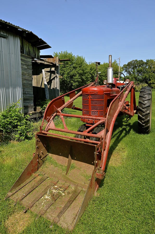 Old tractor with front end loader. Ann old red restored tractor with a hydraulic front end loader stock images