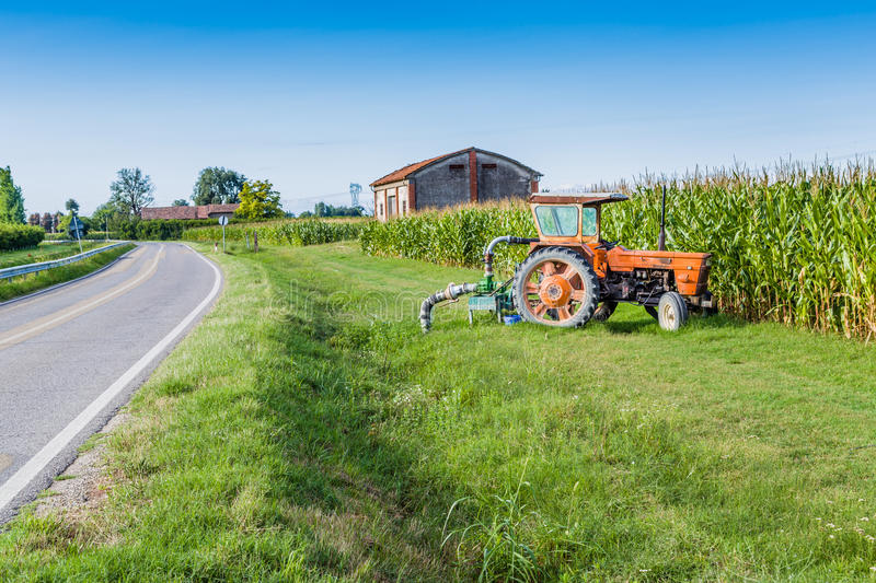 Old tractor in front of a wheat field. Orange old tractor used for irrigation of a cornfield in the Italian countryside stock image