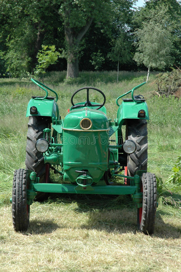 Old tractor. Old green tractor in the meadow stock image