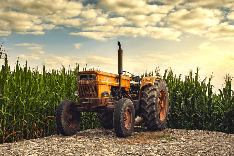 Old tractor near farm fields royalty free stock photography