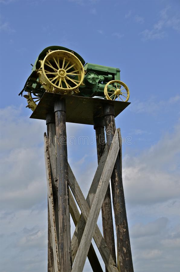 Old tractor perched for display. An very old tractor is placed on a platform supported by heavy beams for display purposes royalty free stock images