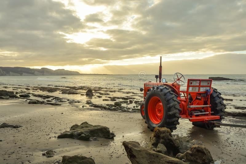 Old tractor standing on the beach near Cape Kidnappers. Napier, New Zealand - February 14, 2015: Old tractor standing on the beach near Cape Kidnappers close to stock photo