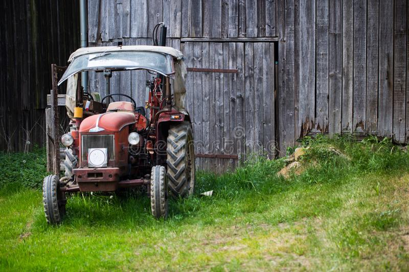 Old Tractor standing in front of barn. Farmer stock photos