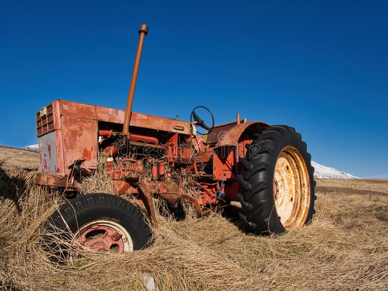 Old tractor standing on a meadow in the high grass. An old red tractor is standing on a brown meadow in the high grass royalty free stock photography
