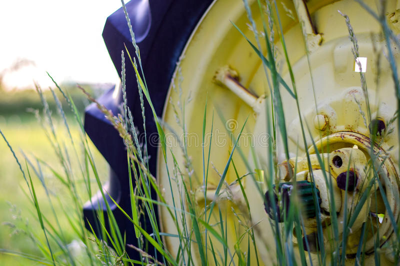 Old Tractor Wheel Behind Blades Of Grass stock photos
