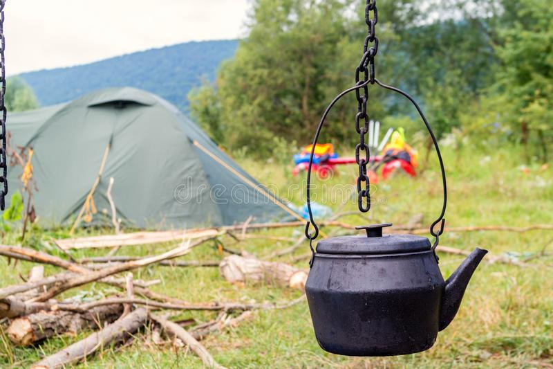 Old traditional black teapot on campfires during camping. Trip on a catamaran on a Dniester river royalty free stock image