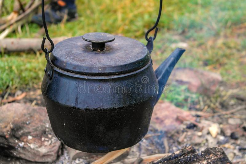 Old traditional black teapot on campfires during camping. Trip on a catamaran on a Dniester river royalty free stock photos