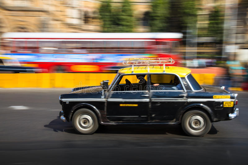 Old traditional black and yellow taxi in movement depicted with motion blur panning royalty free stock photo