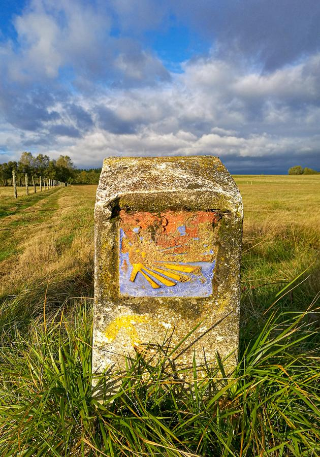 Old traditional camino yellow shell symbol on milestone. On autumn Spanish pasture with cloudy sky. Directional sign for pilgrims in Saint James way. Camino stock photo