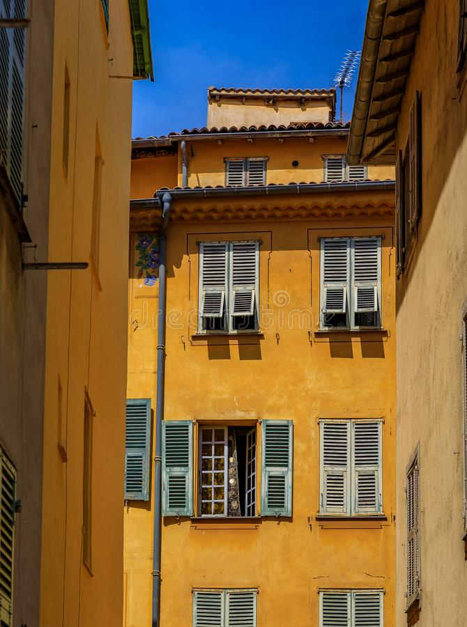 Old traditional houses in the narrow streets in the Old Town Vielle Ville in Nice in the South of France. View of old traditional houses in the narrow streets in royalty free stock photo