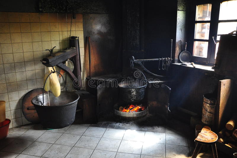 Old traditional kitchen in an Alpine hut. Cheese production in an old alpine hut kitchen in the Carnia region, Friuli Venezia Giulia, Italy. Traditional royalty free stock photography